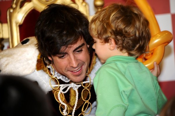 Fernando Alonso (ESP), Ferrari, dressed as a wise man, listens to a young fan.