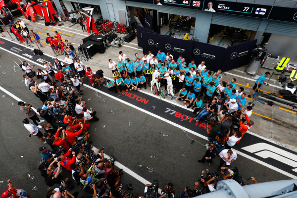 Lewis Hamilton, Mercedes AMG F1, 1st position, Valtteri Bottas, Mercedes AMG F1, 3rd position, and the Mercedes team celebrate as photographers gather for a shot.