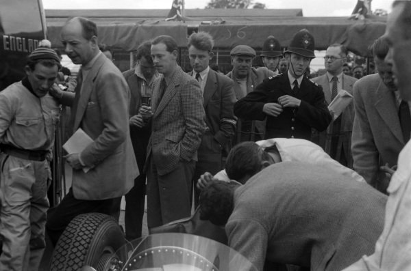 Stirling Moss and Raymond Mays chat, while mechanics work on one of the BRM P15s.