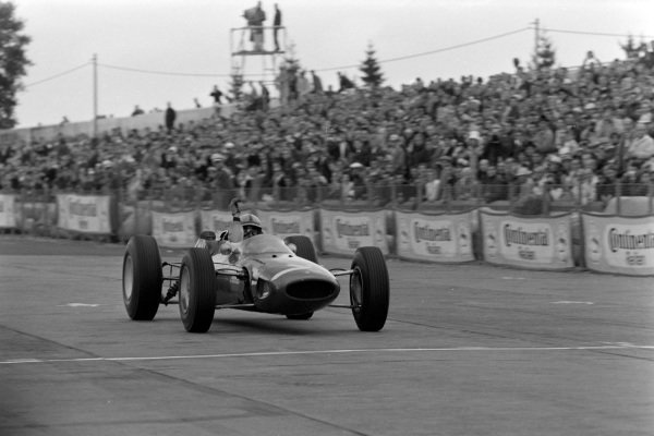 John Surtees, Ferrari 158, crosses the finish line to take victory.