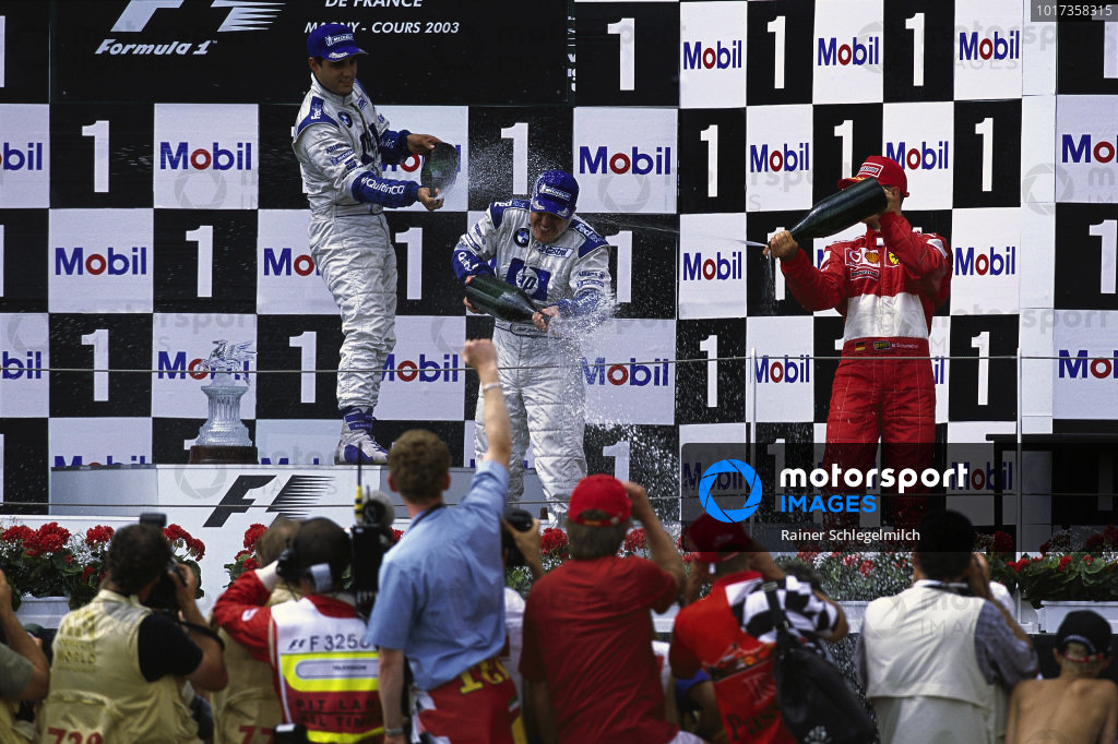 Ralf Schumacher, 1st position, Juan Pablo Montoya, 2nd position, and Michael Schumacher, 3rd position, celebrate on the podium.