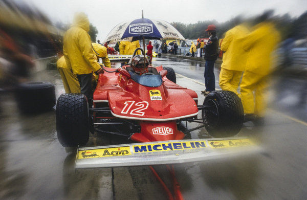Gilles Villeneuve keeps dry in the pit lane whilst sat in his Ferrari 312T4.
