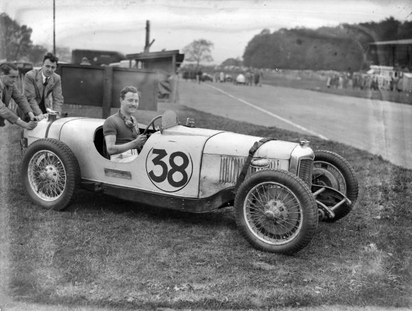 A driver sits in his Riley by the side of the track.