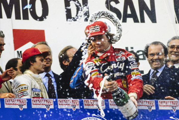 Didier Pironi, 1st position, sprays champagne in celebration on the podium. Gilles Villeneuve, 2nd position, walks away in disgust at his team-mate's actions during the race.