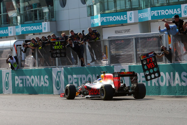 Race winner Daniel Ricciardo (AUS) Red Bull Racing RB12 crosses the line to win the race and celebrate with the team on the pitwall at Formula One World Championship, Rd16, Malaysian Grand Prix, Race,  Sepang, Malaysia, Sunday 2 October 2016.
