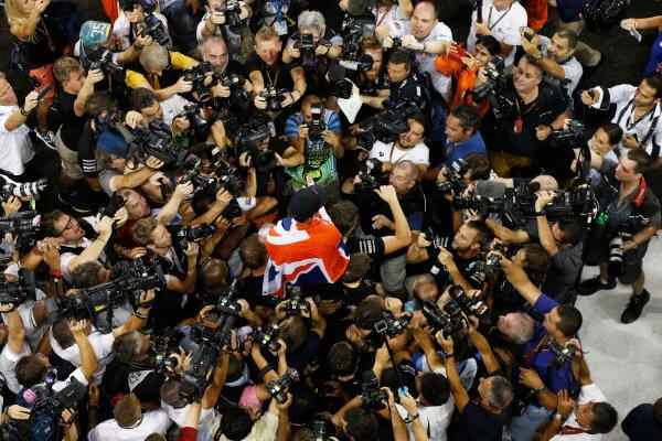 Yas Marina Circuit, Abu Dhabi, United Arab Emirates. Sunday 23 November 2014. Lewis Hamilton, Mercedes AMG, 1st Position, celebrates with his team. World Copyright: Charles Coates/LAT Photographic. ref: Digital Image _J5R7460