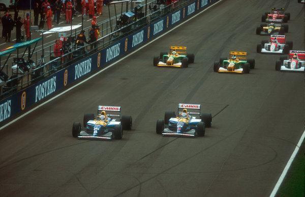 1992 British Grand Prix.Silverstone, England.10-12 July 1992.Riccardo Patrese beats poleman and teammate Nigel Mansell (both Williams FW14B Renault's) away at the start, followed by Michael Schumacher, Martin Brundle (both Benetton B192 Ford's), Ayrton Senna, Gerhard Berger (both McLaren MP4/7A Honda's), Johnny Herbert (Lotus 107 Ford) and Jean Alesi (Ferrari F92A).Ref-92 GB 09.World Copyright - LAT Photographic