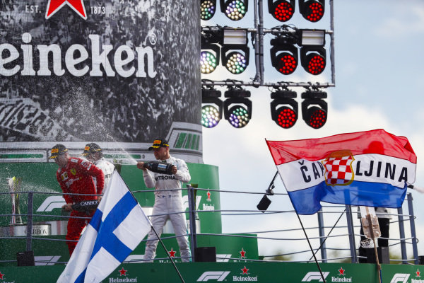 Charles Leclerc, Ferrari, 1st position, Valtteri Bottas, Mercedes AMG F1, 2nd position, and Lewis Hamilton, Mercedes AMG F1, 3rd position, celebrate with Champagne on the podium