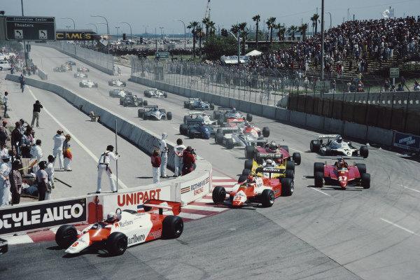 Niki Lauda, McLaren MP4-1B Ford, leads Bruno Giacomelli, Alfa Romeo 182, Alain Prost, Renault RE30B, Gilles Villeneuve, Ferrari 126C2, Didier Pironi, Ferrari 126C2, Keke Rosberg, Williams FW07C Ford, and the rest of the pack..