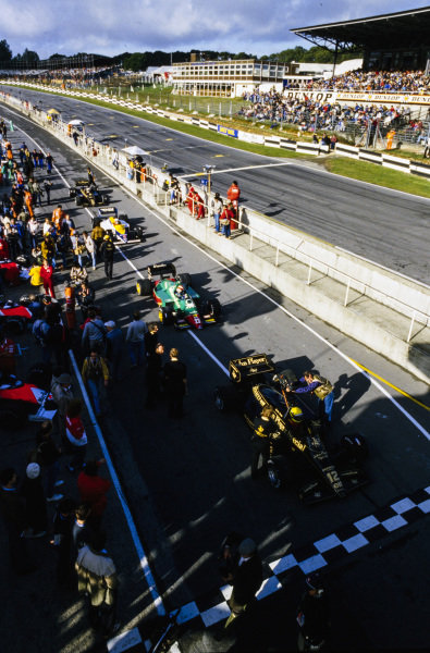Ayrton Senna, Lotus 97T Renault, sat ahead of Eddie Cheever, Alfa Romeo 184T, Nigel Mansell, Williams FW10 Honda, and Elio de Angelis, Lotus 97T Renault, at the end of the pitlane.