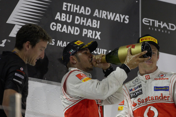 Lewis Hamilton, 1st position, celebrates on the podium alongside Andy Latham and Jenson Button, 3rd position.