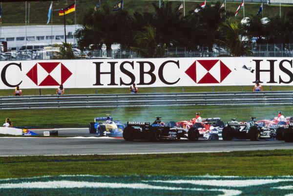 Jarno Trulli, Renault R23, is spun round at the start, by Michael Schumacher, Ferrari F2002.