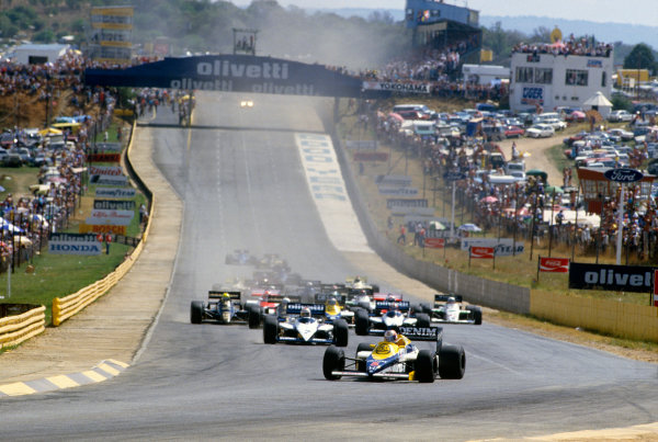 Kyalami, South Africa. 17-19 October 1985. Nigel Mansell (Williams FW10 Honda) leads Nelson Piquet and Marc Surer (both Brabham BT54 BMW's) at the start. Ref: 85 SA 07. World Copyright - LAT Photographic
