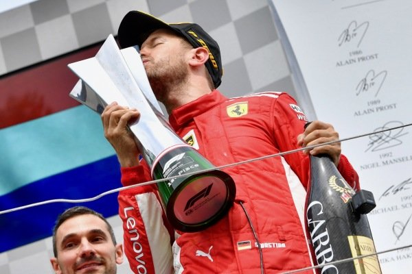 Race winner kisses the trophy and celebrates on the podium
