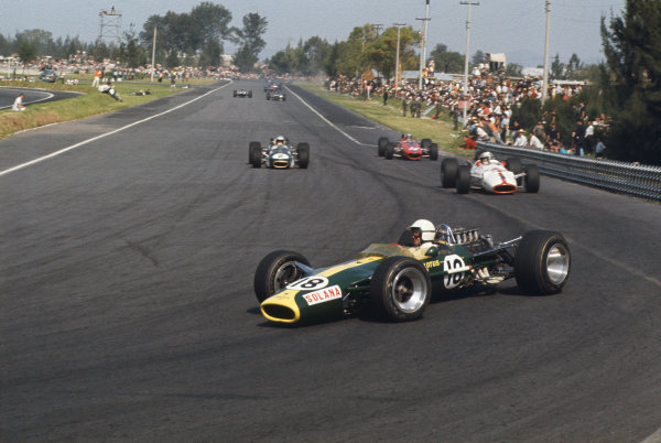 Mexico City, Mexico. 20 - 22 October 1967.  Moises Solana (Lotus 49 Ford) leads John Surtees (Honda RA300), Denny Hulme (Brabham BT24 Repco) and Bruce McLaren (McLaren M5A BRM) into the hairpin.  Ref: 67MEX01. World Copyright: LAT Photographic