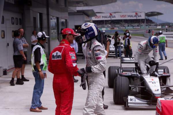 Sepang, Kuala Lumpur, Malaysia.20-22 October 2000.David Coulthard (McLaren Mercedes) congratulates Michael Schumacher (Ferrari) on taking pole position, in parc ferme after the qualifying session.ref: digital imageWorld Copyright - LAT Photographic