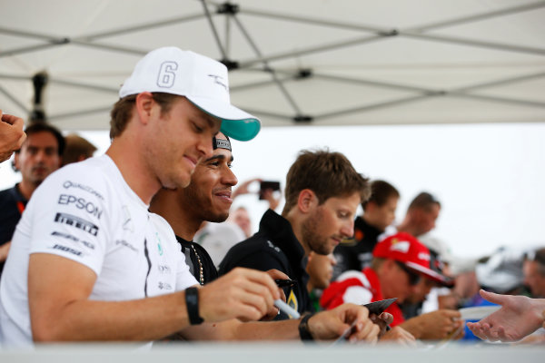 Hungaroring, Budapest, Hungary. Thursday 23 July 2015. Nico Rosberg, Mercedes AMG, Lewis Hamilton, Mercedes AMG, and Romain Grosjean, Lotus F1, sign autographs for fans. World Copyright: Charles Coates/LAT Photographic ref: Digital Image _J5R0504
