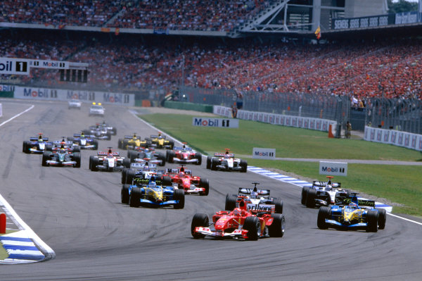 2004 German Grand Prix Hockenheim, Germany. 23rd - 25th July. Michael Schumacher, Ferrari F2004 leads the field into the first corner followed by the quick starting Fernando Alonso, Renault R24. Action.  World Copyright:Charles Coates/LAT Photographic  Ref:35mm Image:A03