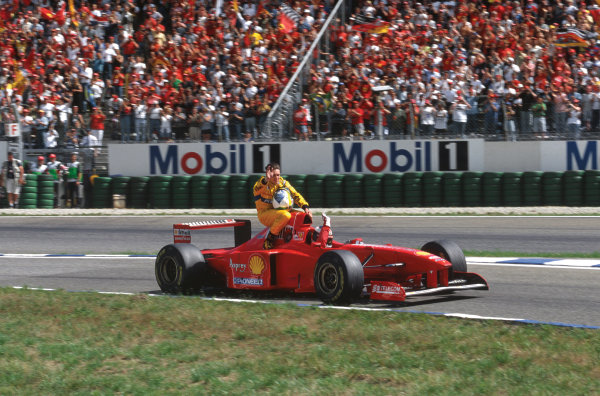 . Hockenheim, Germany. 25-27 July 1997. Michael Schumacher (Ferrari F310B) 2nd position, gives Giancarlo Fisichella a lift back to the pits aboard his car, action.  World Copyright: LAT Photographic. Ref:  97 GER 05