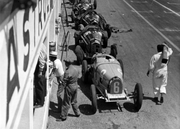 "1934 Marne Grand Prix Reims, France. 8 July 1934 The cars of Robert Brunet, Bugatti T51, Guy Moll, Alfa Romeo Tipo-B ""P3"", Achille Varzi, Alfa Romeo Tipo-B ""P3"" and Louis Chiron, Alfa Romeo Tipo-B ""P3"", in the pits, atmosphere World Copyright: Robert Fellowes/LAT PhotographicRef: 34REI05"