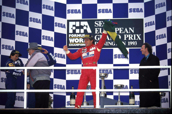Ayrton Senna, 1st position, with the Brazilian flag on the podium.  Tom Wheatcroft congratulates Alain Prost, 3rd position, on the left of frame.