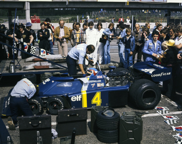 Patrick Depailler's Tyrrell P34 Ford waits alongside the weighbridge in the paddock as Depailler himself signs autographs for fans.