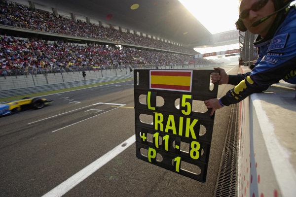 A mechanic holds out Fernando Alonso's pit board.