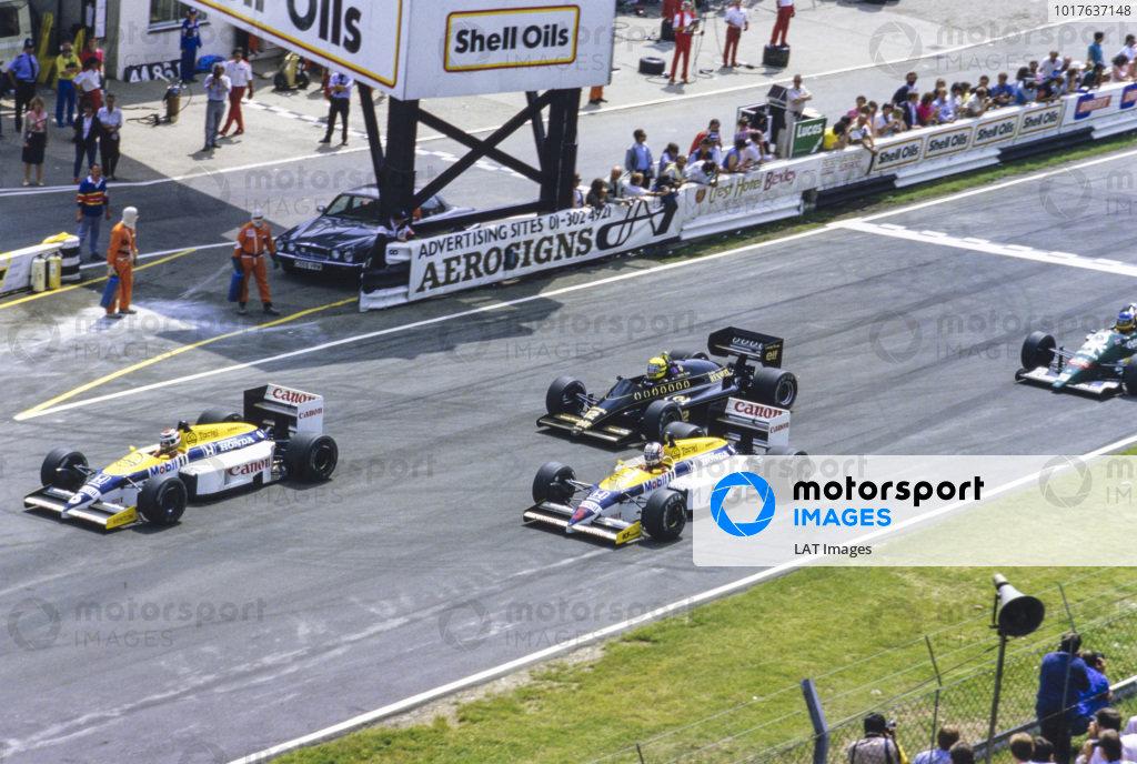 Nelson Piquet, Williams FW11 Honda, leads Nigel Mansell, Williams FW11 Honda, and Ayrton Senna, Lotus 98T Renault, at the start.