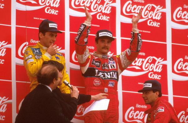 Imola, Italy.1-3 May 1987.Nigel Mansell (Williams Honda) 1st position, Ayrton Senna (Lotus Honda) 2nd position and Michele Alboreto (Ferrari) 3rd position on the podium.Ref-87 SM 07.World Copyright - LAT Photographic