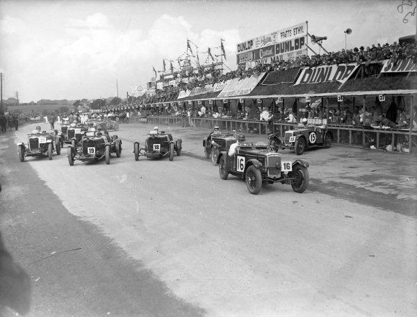 N. A. Berry, Frazer Nash TT Replica, leads T. S. Fothringham-Parker, Aston Martin Ulster (#18), Pat Driscoll, Aston Martin Ulster (#19), and J. D. Barnes, Singer (#21), at the start.