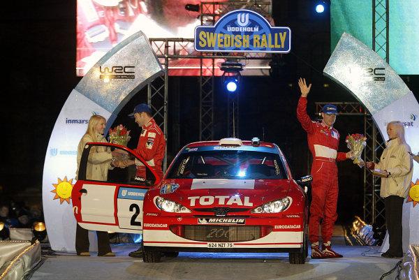 2003 FIA World Rally Championship.  Karlstad, Sweden. Rd2. 6-9 February 2003. Richard Burns/Robert Reid (Peugeot) celebrate 3rd position on the podium.  World Copyright: McKlein/LAT Photographic
