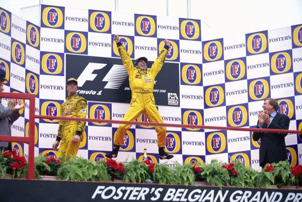 Damon Hill, 1st position, celebrates on the podium while teammate Ralf Schumacher, 2nd position, looks on.