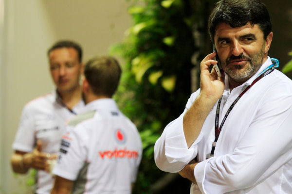 Marina Bay Circuit, Singapore. Friday 20th September 2013. Luis Garcia Abad, Manager of Fernando Alonso talks on a mobile phone near the McLaren team in the paddock. World Copyright: Charles Coates/LAT Photographic. ref: Digital Image _X5J8921