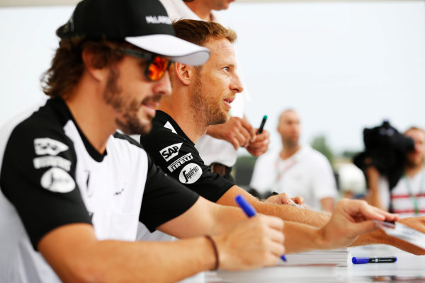 Hungaroring, Budapest, Hungary. Thursday 23 July 2015. Jenson Button, McLaren, and Fernando Alonso, McLaren, sign autographs for fans. World Copyright: Charles Coates/LAT Photographic ref: Digital Image _J5R0887