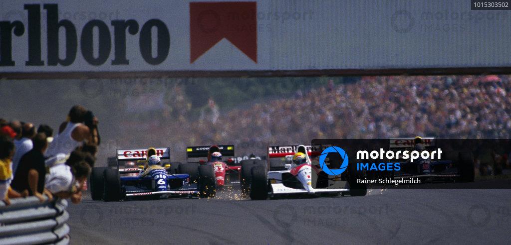 Ayrton Senna, McLaren MP4-6 Honda, with sparks flying as he brakes, leads Riccardo Patrese, Williams FW14 Renault, Alain Prost, Ferrari 643, and Nigel Mansell, Williams FW14 Renault, into the first corner at the start.