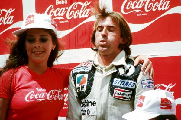 Race winner Jacques Laffite (FRA) Ligier takes a deep breath on the podium as he is aided by a Coca-Cola girl.