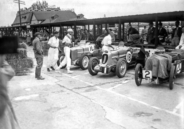 A driver runs to his Austin Seven Sports Ulster TT in the pits.