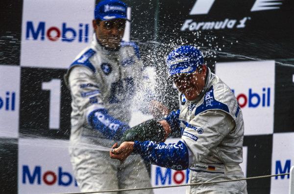Ralf Schumacher, 1st position, celebrates on the podium with Juan Pablo Montoya, 2nd position.