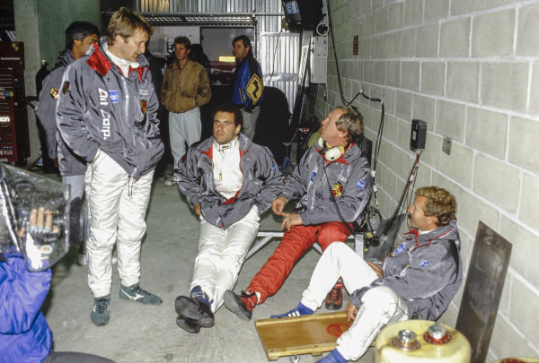 Wiil Hoy, Roland Ratzenberger, Vern Schuppan and another driver chat in the pits.