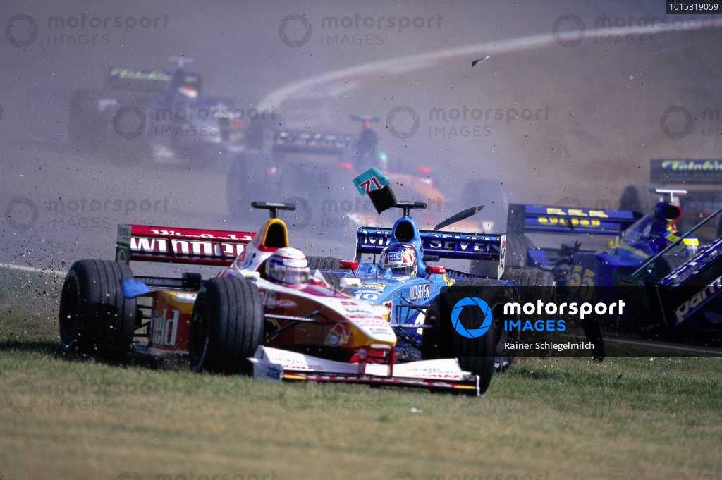 Alex Zanardi, Williams FW21 Supertec, runs wide over the grass as Alex Wurz, Benetton B199 Playlife, crashes out behind him.
