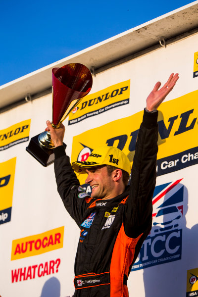 2015 British Touring Car Championship, Silverstone, Northamptonshire, England. 26th - 27th September 2015. Colin Turkington (GBR) Team BMR Volkswagen Passat CC, 1st position, celebrates on the podium. World Copyright: Zak Mauger/LAT Photographic. ref: Digital Image _L0U4828