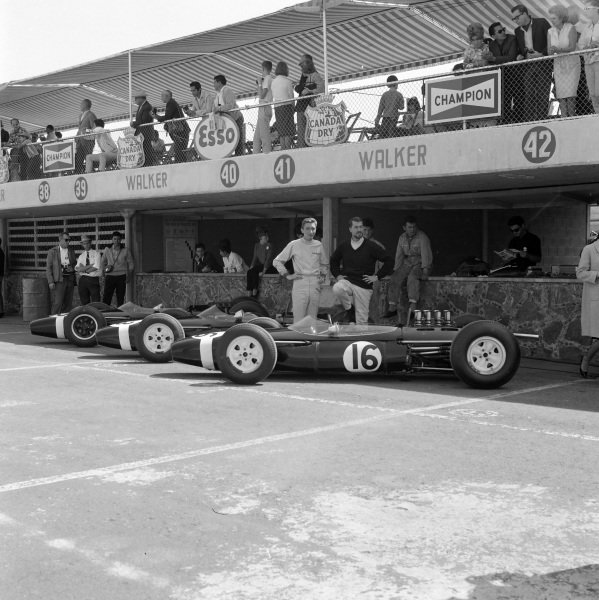 Jo Bonnier stands beside his Brabham BT7 Climax and Jo Siffert with the two Brabham BT11 BRM cars in the pitlane.