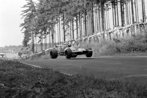 Jacky Ickx, Brabham BT26A Ford, jumps over a crest.