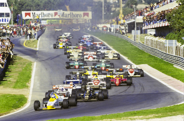 Keke Rosberg, Williams FW09B Honda, leads Nigel Mansell, Lotus 95T Renault, and Alain Prost, McLaren MP4-2 TAG, into the first corner. Further back in the pack, in 13th place, is championship contender Niki Lauda, McLaren MP4-2 TAG.