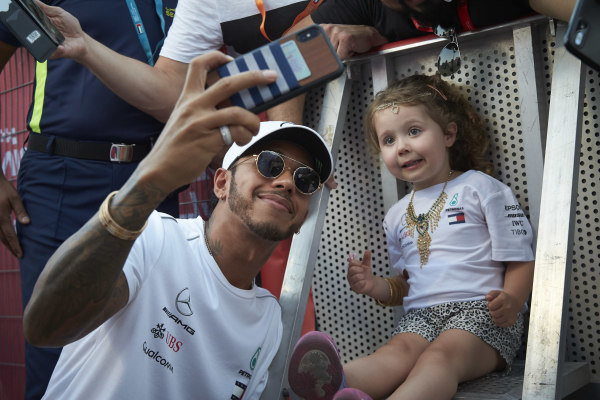 Lewis Hamilton, Mercedes AMG F1, takes a selfie with a small fan