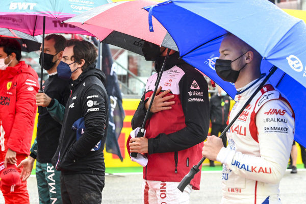 Fernando Alonso, Alpine F1, Antonio Giovinazzi, Alfa Romeo Racing, Nikita Mazepin, Haas F1, and the other drivers stand for the national anthem prior to the start