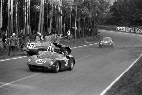 Jean Guichet / Nino Vaccarella, Scuderia Ferrari, Ferrari 275P, and Roberto Bussinello / Bruno Deserti, Scuderia Sant Ambroeus, Alfa Romeo Giulia TZ, pass the crashed car of Fernand Masoero / Jean Rolland, Scuderia Sant Ambroeus, Alfa Romeo Giulia TZ, as Roberto Bussinello / Bruno Deserti, Scuderia Sant Ambroeus, Alfa Romeo Giulia TZ, approaches.