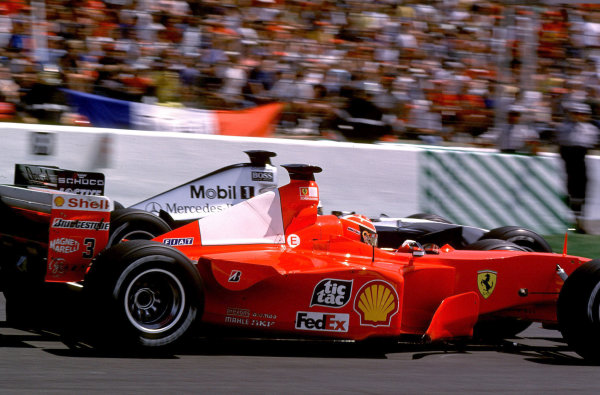 2000 French Grand Prix.Magny-Cours, France. 30/6-2/7 2000.Michael Schumacher (Ferrari F1-2000) and David Coulthard (McLaren MP4/15 Mercedes) battle for the lead on the approach to the Hairpin.World Copyright - LAT PhotographicFormat: 35mm transparency