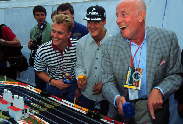 1995 British Grand Prix.Silverstone, England. 14-16 July 1995.Johnny Herbert and Michael Schumacher play Scalextric with actor Richard Wilson at a pre-race Benetton Renault party.World Copyright - LAT Photographic