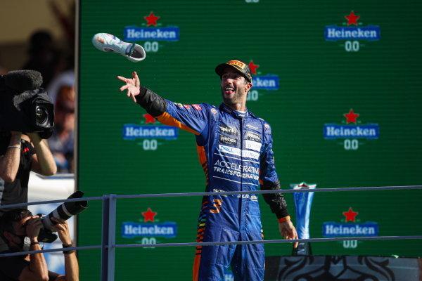 Daniel Ricciardo, McLaren, 1st position, takes his boot off for a shoey